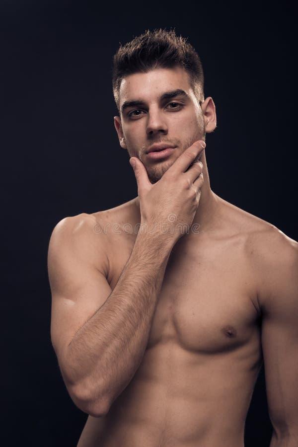 Één jonge mens die, knap, camera, shirtless handgezicht bekijken stock foto