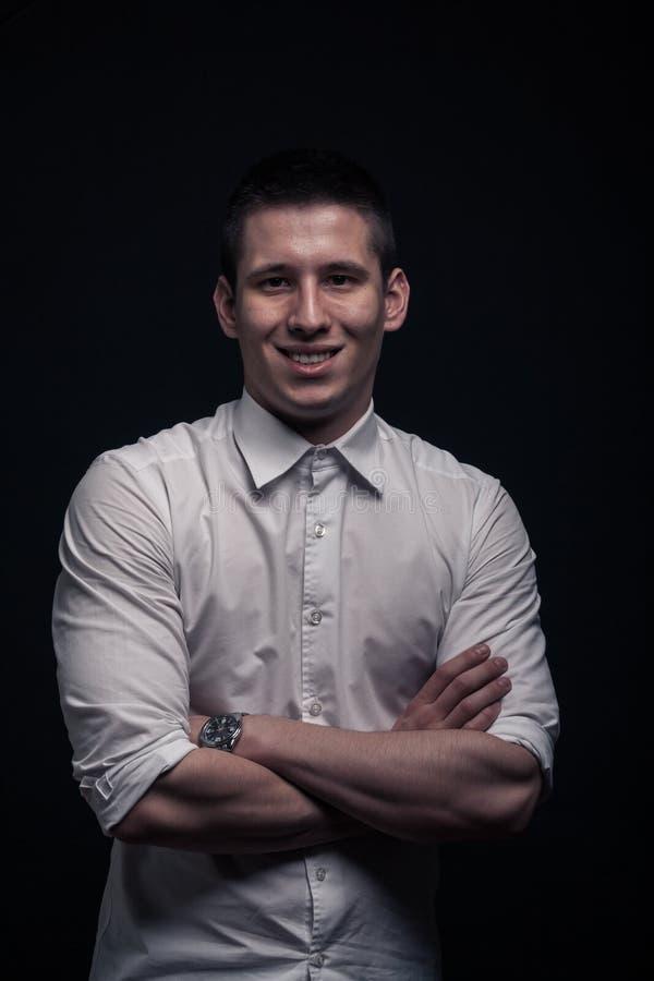 Één jonge mens, gelukkig, het glimlachen, gekruiste wapens, hoger lichaamsportret royalty-vrije stock fotografie