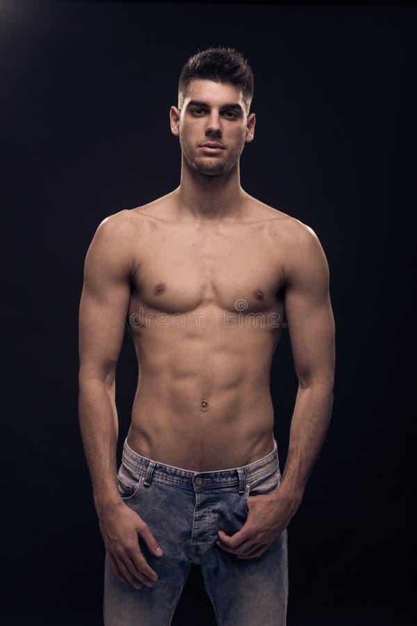 Één jonge mens het stellen, jeans shirtless abs lichaam stock foto