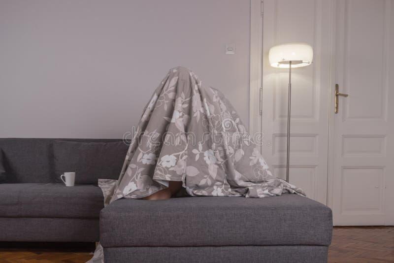Één jonge mens, onder bedbladen het verbergen royalty-vrije stock fotografie