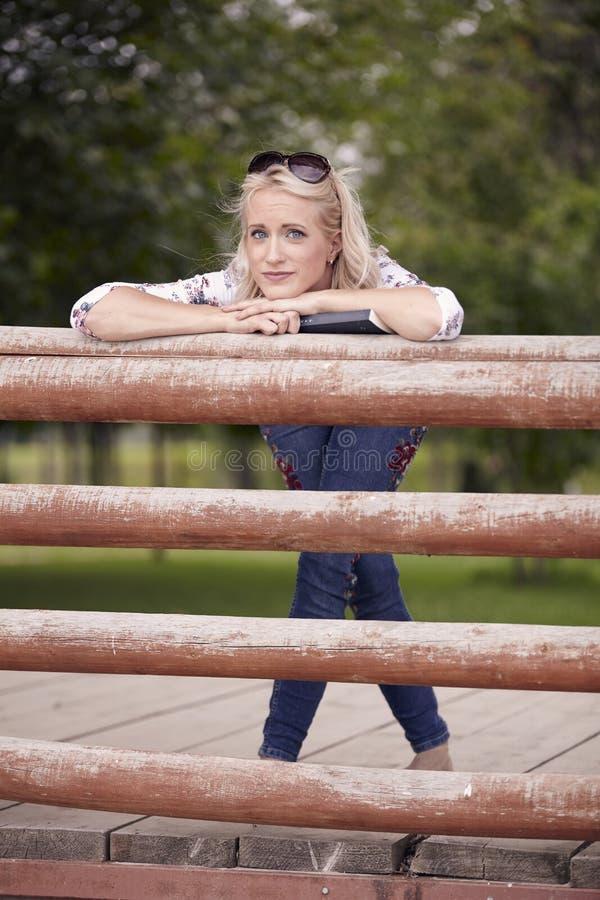Één jonge mooie vrouw, 25 jaar oud, droevig portret, die op houten omheining, openlucht in park leunen royalty-vrije stock foto's