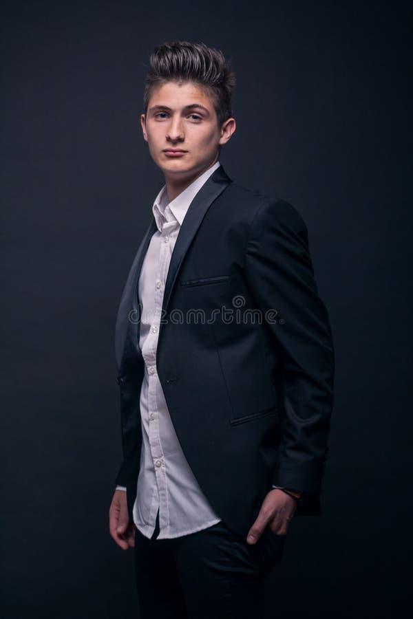 Één jonge tiener, die het overhemd van het kostuumjasje, hoger lichaam dragen stock foto