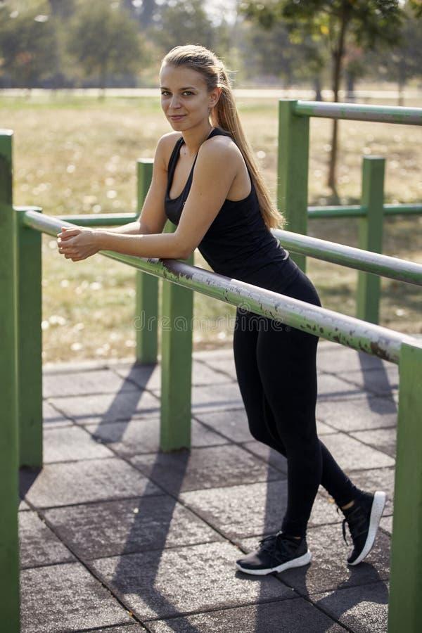 Één jonge vrouw, 20-29 jaar oud, het stellen, die op de bars van het oefeningsmateriaal, openbare gymnastiek in openlucht leunen royalty-vrije stock afbeeldingen