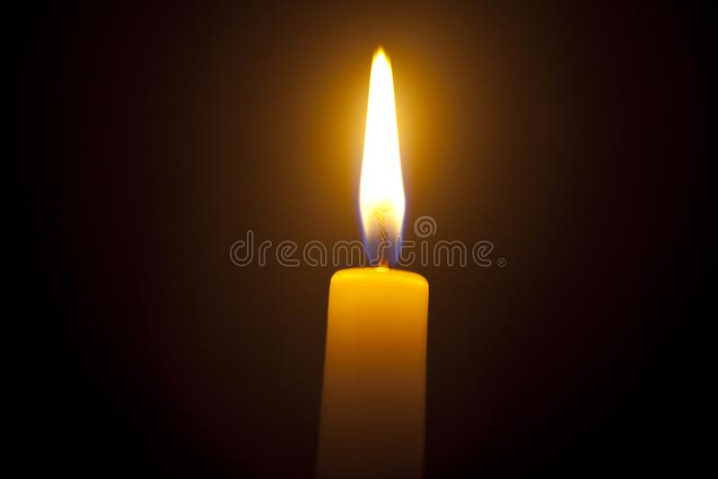 Één kaarslicht in dark stock foto's