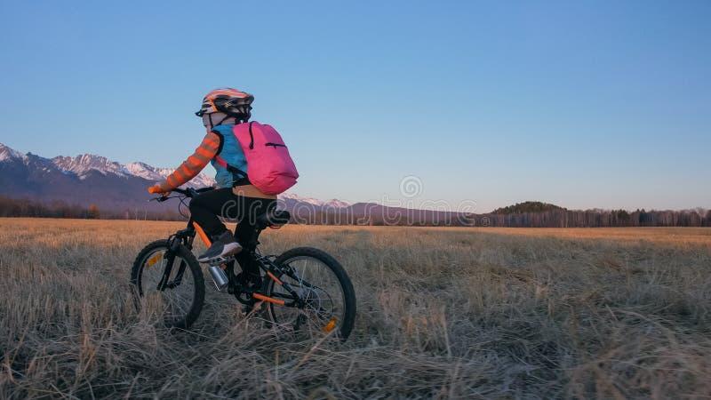 Één Kaukasische fiets van kinderenritten op tarwegebied Meisje die zwarte oranje cyclus berijden op achtergrond van mooie sneeuw royalty-vrije stock afbeeldingen