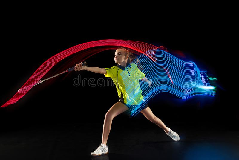 Één Kaukasische jonge speler van het de vrouwen speelbadminton van het tienermeisje op zwarte achtergrond stock afbeeldingen