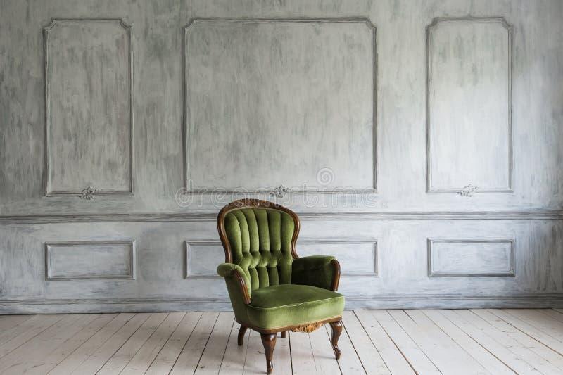 Één klassieke leunstoel tegen een witte muur en een vloer De ruimte van het exemplaar stock foto