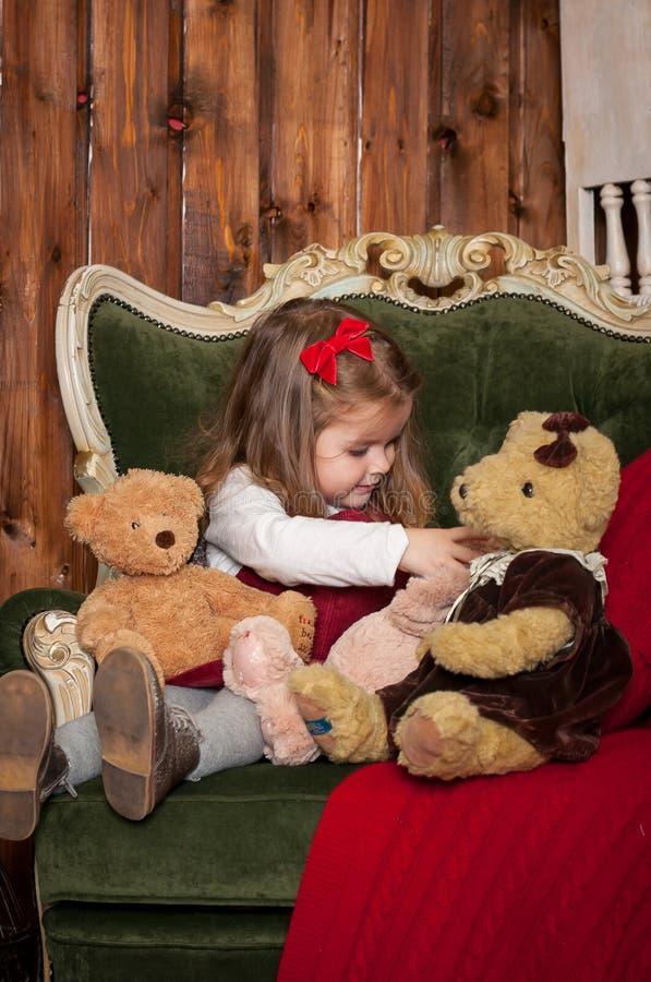 Één klein Kaukasisch leuk meisje dat in de feestelijke Nieuwe ruimte van de jaarstudio met teddyberen glimlacht royalty-vrije stock afbeelding