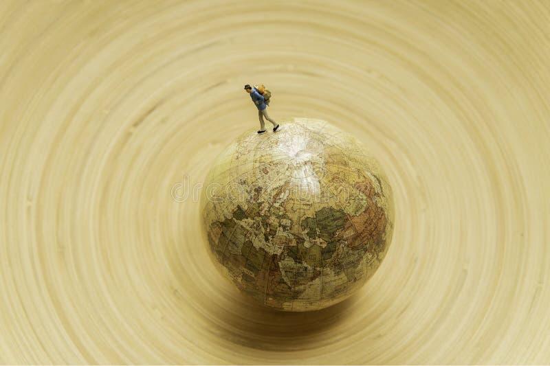 Één kleine modelreizigersgang rond de kaart van de bolwereld in houten kom stock foto