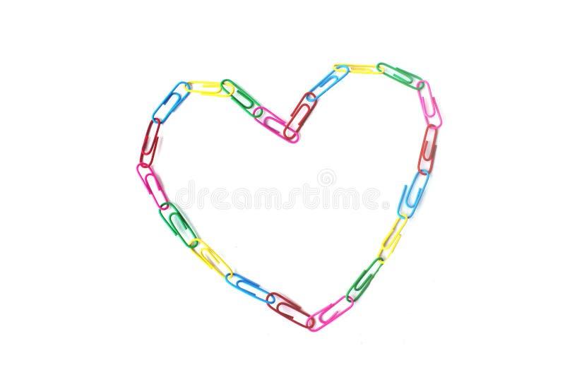Één kleurrijk hart van paperclips op het wit stock afbeeldingen
