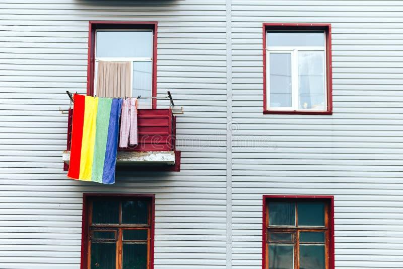 Één kleurrijke handdoek hangt om balkon van grijs huis, langs individualiteitsconcept, heldere vlek op grijze achtergrond royalty-vrije stock foto