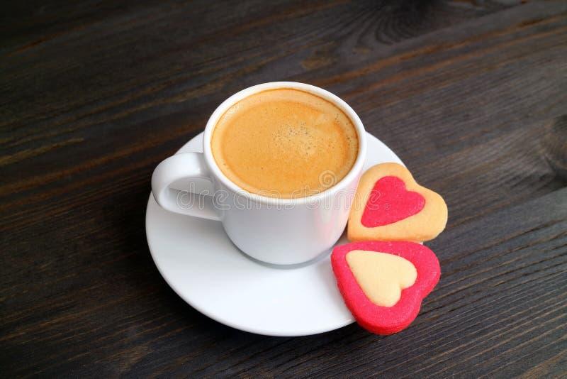Één kop van hete koffie met een paar van hart vormde koekjes op donkere kleuren houten lijst stock foto's