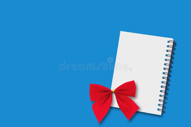 Één leeg document notitieboekje met spiraalvormige draad en rode feestelijke textiel bond boog op blauwe lijst exemplaar ruimte v vector illustratie
