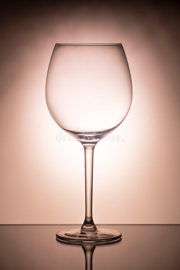 Één leeg wijnglas voor rode wijn op verspreiding aangestoken achtergrond royalty-vrije stock afbeeldingen