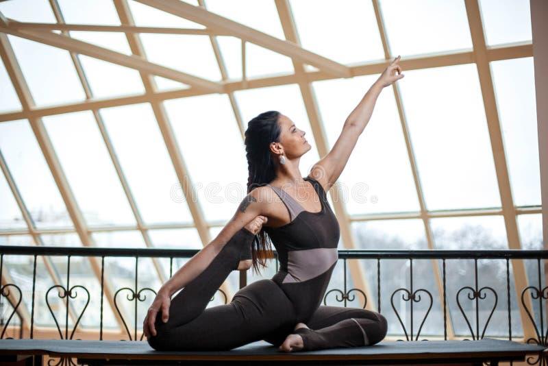 Één legged houding van de koningsduif van yoga Rajakapotasana voor grote vensters stock foto's