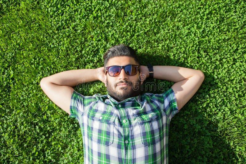 Één maniermens van het Middenoosten met baard, de stijl van het manierhaar rust op de mooie groene tijd van de grasdag stock afbeelding