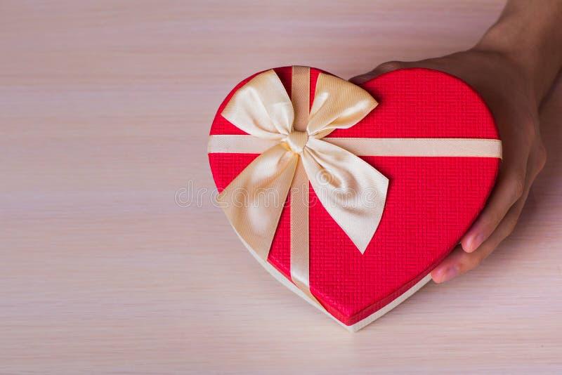 Één mannelijke hand die rode giftdoos in vorm van hart houden royalty-vrije stock foto's