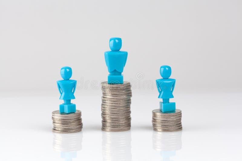 Één mannetje en twee vrouwelijke beeldjes die zich op stapels van muntstukken bevinden royalty-vrije illustratie