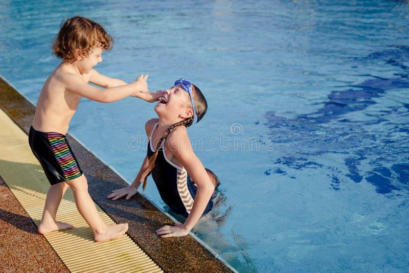 Één meisje en weinig jongen die in de pool spelen stock afbeeldingen