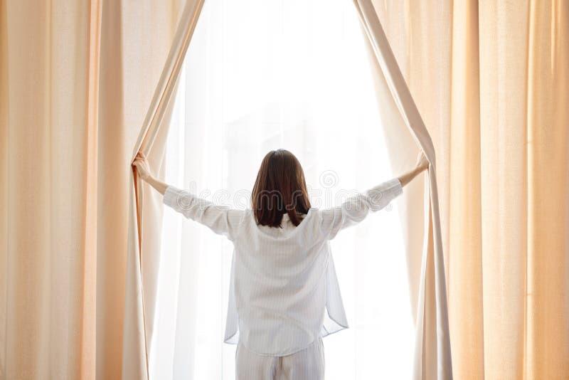 Één meisje in lichte pyjama's opent gordijnen royalty-vrije stock afbeelding