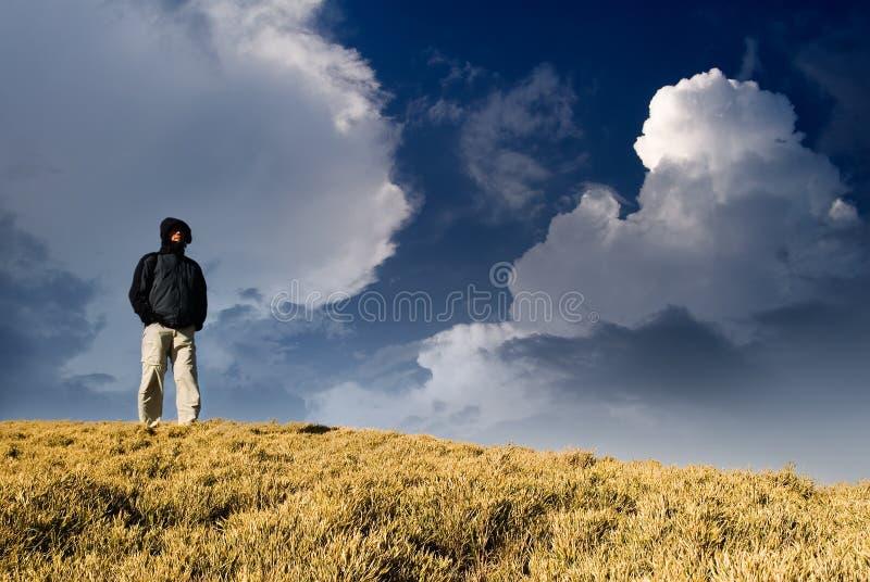 Één mens die zich op de heuvel bevindt royalty-vrije stock afbeelding
