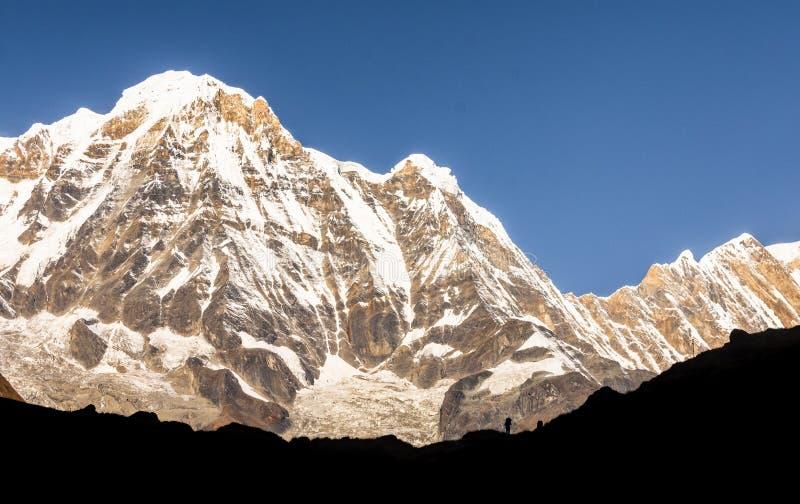 Één mens die zich voor Annapurna-Zuiden, Himalayagebergte bevinden royalty-vrije stock afbeelding