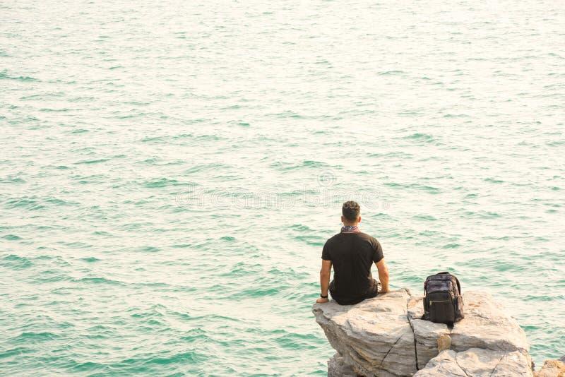 ??n mens leunt achterover in op rots door het overzees met rugzak royalty-vrije stock foto