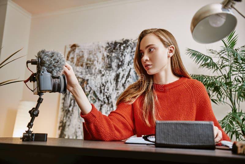 Één minuut Het portret van vrouwelijke bloggervestiging haar driepoot zette digitale camera op terwijl thuis het maken van een ni royalty-vrije stock afbeeldingen