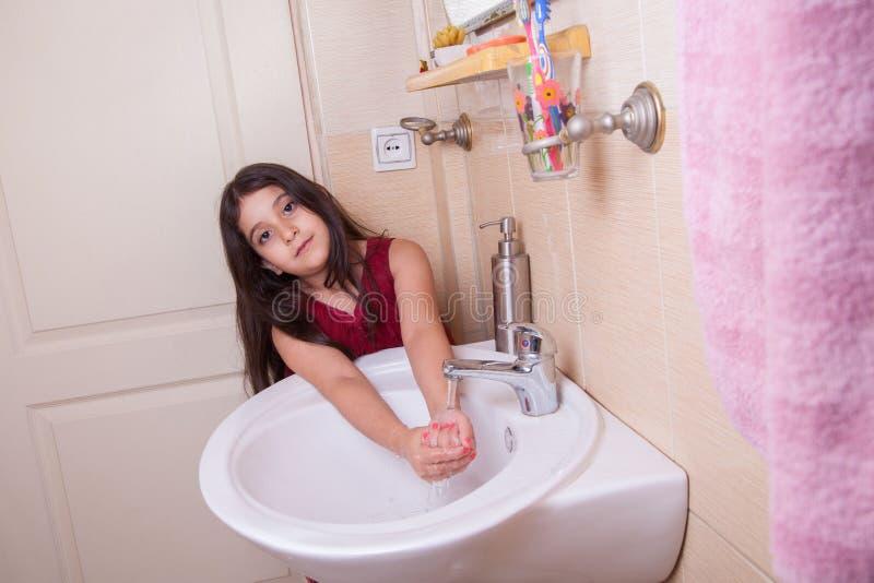 Één mooi klein Arabisch meisje van het Middenoosten met rode kleding wast haar indient de badkamers stock foto's