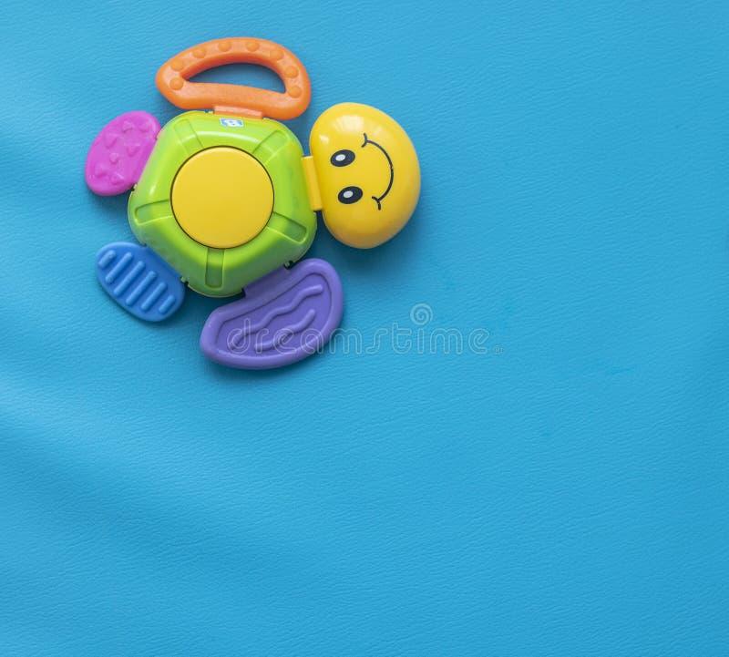 Één multi-colored stuk speelgoed schildpad met een glimlach op een blauwe achtergrond van de linkerzijde stock fotografie