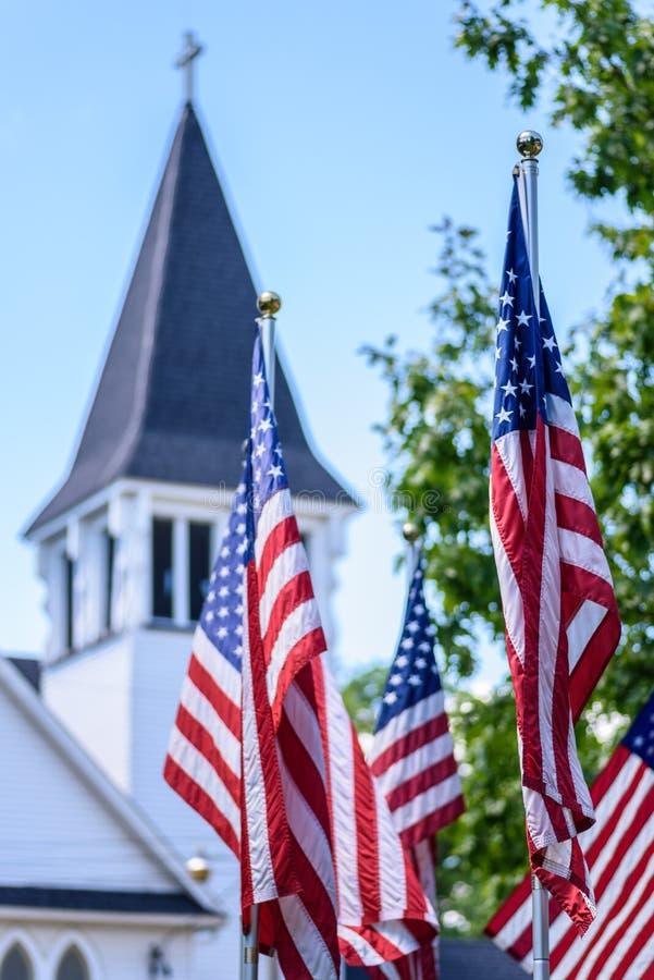 Één natie onder God - de vlaggen van de V.S. voor witte kerktorenspits stock foto's