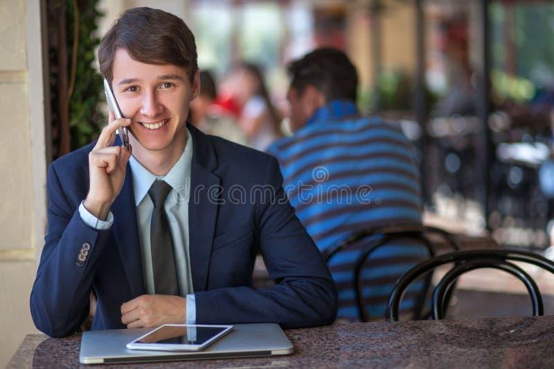 Één ontspande het jonge knappe professionele zakenman werken met zijn laptop, telefoon en tablet in een lawaaierige koffie stock foto's