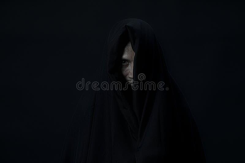 Één oog van de mens in zwarte dekking die aan camera op zwarte backgro kijken royalty-vrije stock fotografie