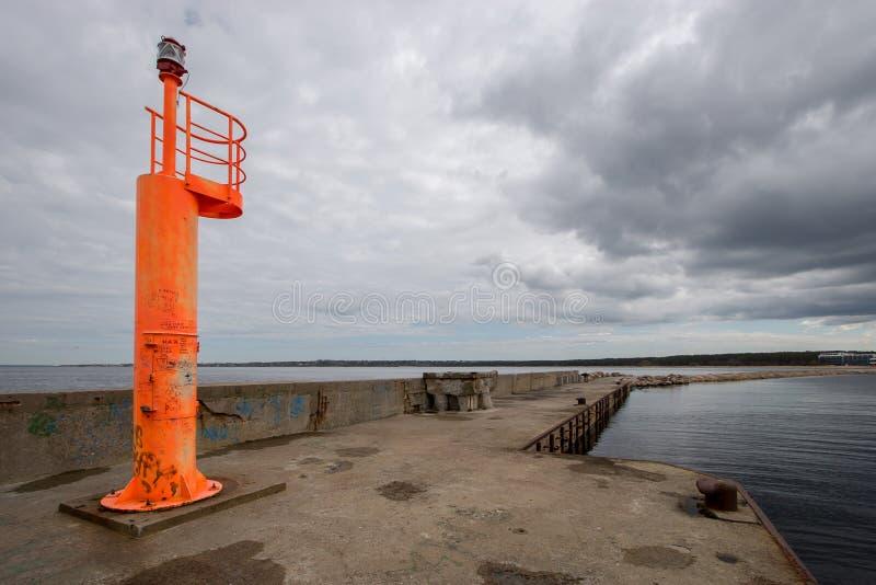 Één oranje vuurtoren bevindt zich op een concrete pijler op de achtergrond van een donkere hemel met wolken royalty-vrije stock foto