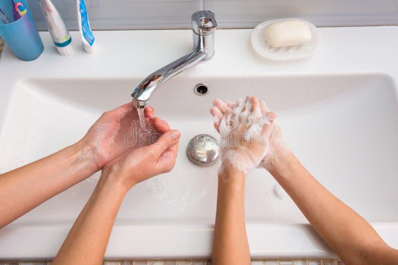 Één paar handen reinigt schuim, een ander paar handenzepen stock foto's