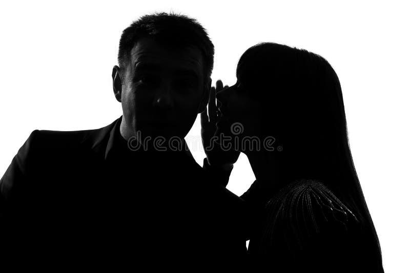 Één paarman en vrouw die bij oor fluisteren stock foto's