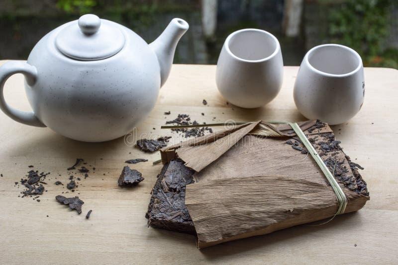 Één pak van zwarte Chinese thee met witte waterketel en twee koppen royalty-vrije stock foto's