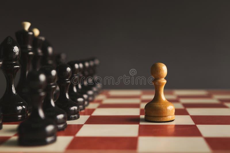 Één pand die zich tegen reeks van zwart schaak bevinden royalty-vrije stock afbeelding