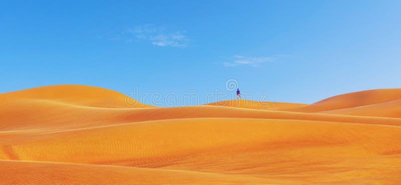 """Één persoon bovenop mooie rode woestijnduinen De toerist die alleen woestijn in Doubai †onderzoeken """"ontdekt het panorama †va royalty-vrije stock fotografie"""