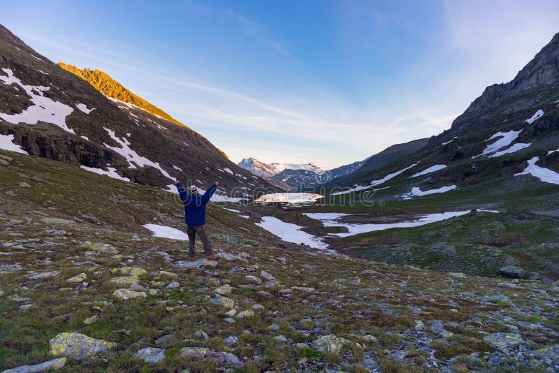 Één persoon die kleurrijke zonsopgang omhoog hoog in de Alpen bekijken Brede hoekmening van hierboven met gloeiende bergpieken in stock foto's