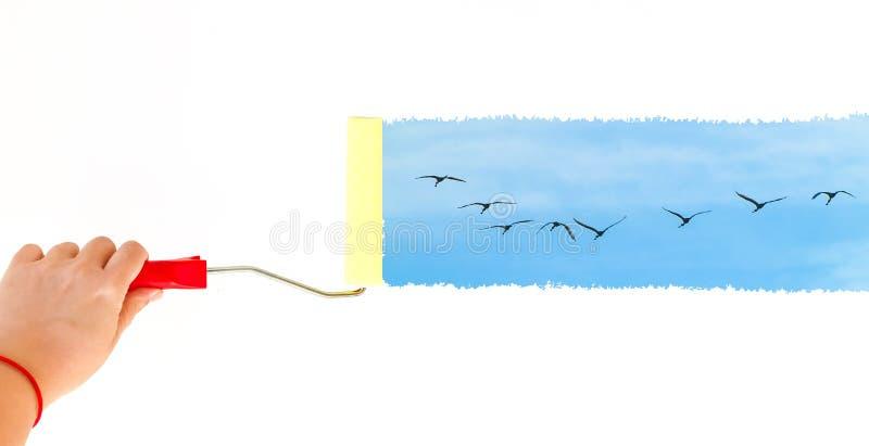 Één persoon het schilderen vogels die op de hemel op een witte muur met een rolborstel vliegen stock fotografie