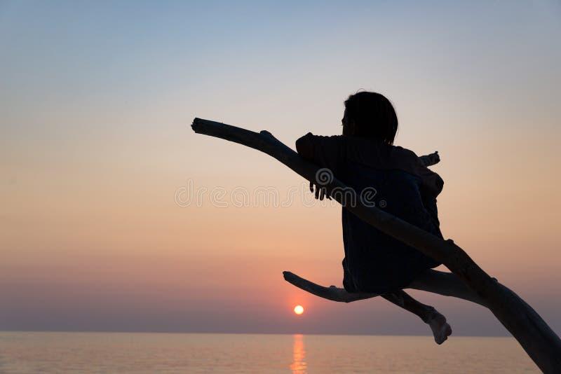 Één persoonszitting op het strand romantische hemel van het takzand bij zonsondergang, achtermeningssilhouet, gouden zonlicht, ec stock afbeelding