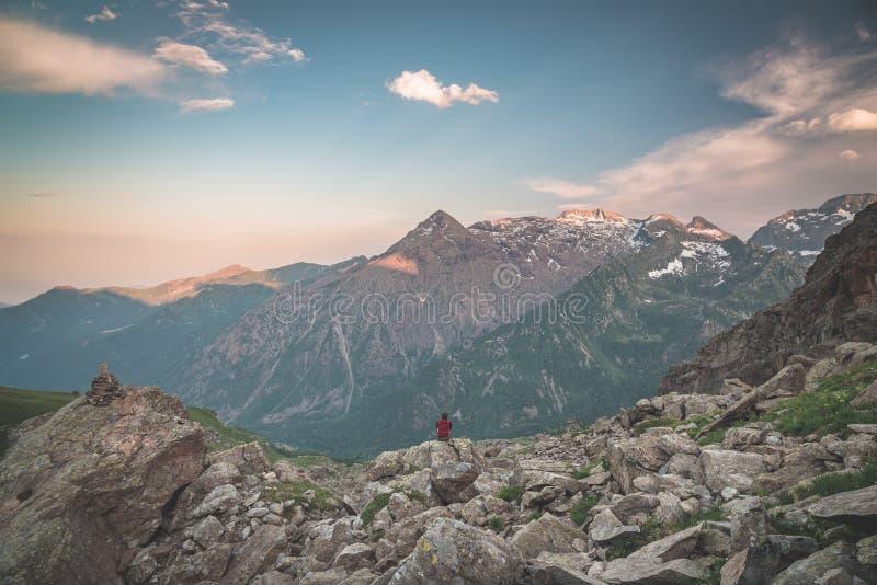 Één persoonszitting op rotsachtig terrein en omhoog het letten van een op kleurrijke zonsopganghoogte in de Alpen Brede hoekmenin royalty-vrije stock foto's