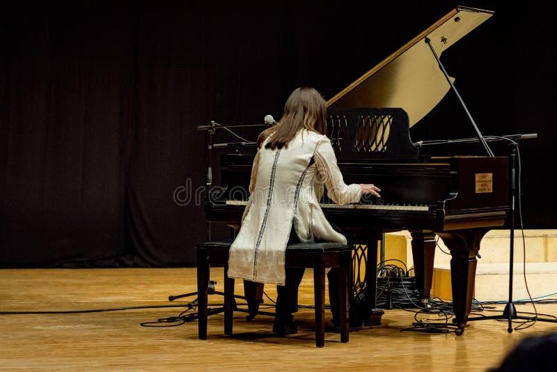 Één piano van vrouwenspelen in een overleg stock fotografie