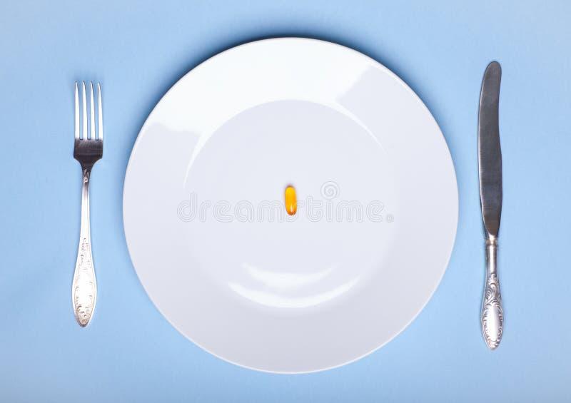 Één pil op witte dinerschotel met tafelgereedschap op blauwe achtergrond royalty-vrije stock fotografie