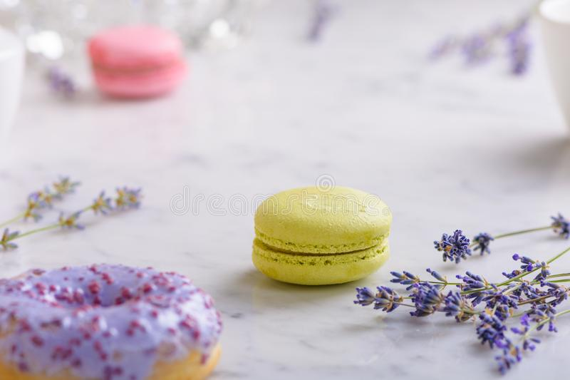 Één pistache macaron en twijgenlavendel in het centrum van het beeld, één lilac doughnut in voorzijde, één roze macaron erachter, royalty-vrije stock foto