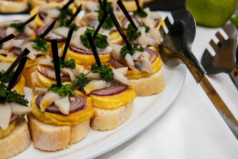 Één plaat met snacks op een buffetlijst De selectie van smakelijke bruschetta of canapes op geroosterde baguette met aardappelsha royalty-vrije stock foto