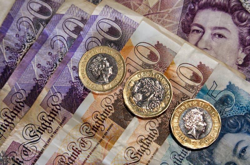 Één pondmuntstukken en bankbiljetten stock afbeelding
