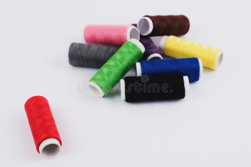 Één rode spoel van draad dichtbij hoop van spoelen van nieuwe kleurrijke draden stock afbeelding