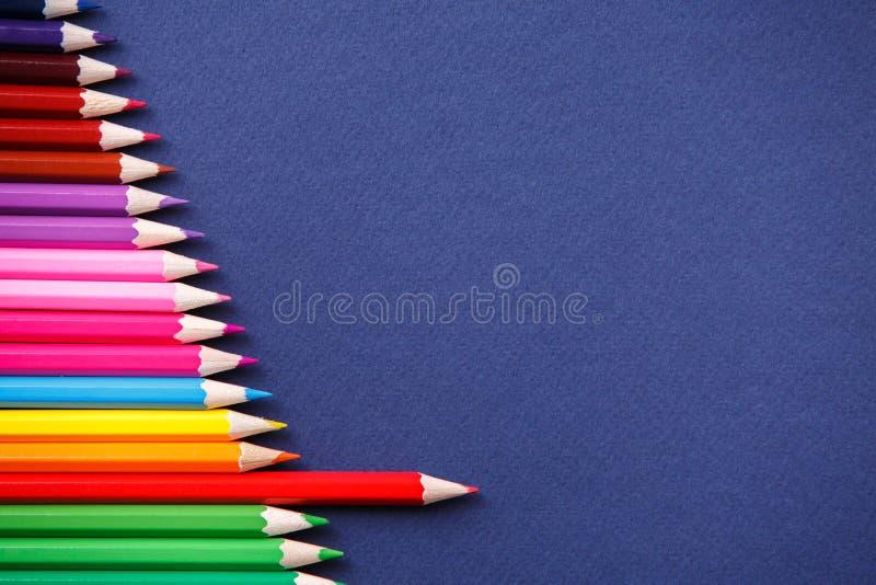 Één rood potlood die van de reeks kleurrijke potloden duidelijk uitkomen Op blauwe achtergrond royalty-vrije stock foto